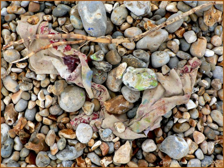 Artist's paint rags on beach pebbles