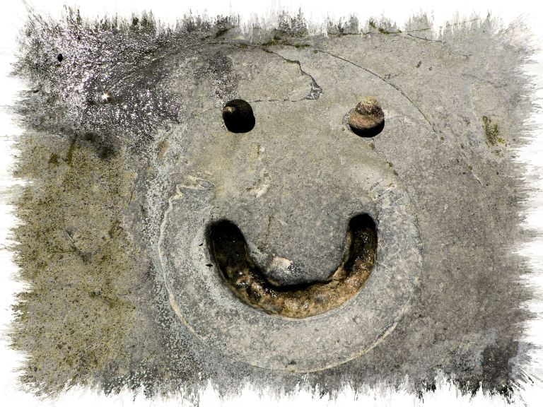 Beach Art 2: Smiling face with ammonite fossil and two winkles at Lyme Regis, Dorset, UK - part of the Jurassic Coast - 04.06.2008