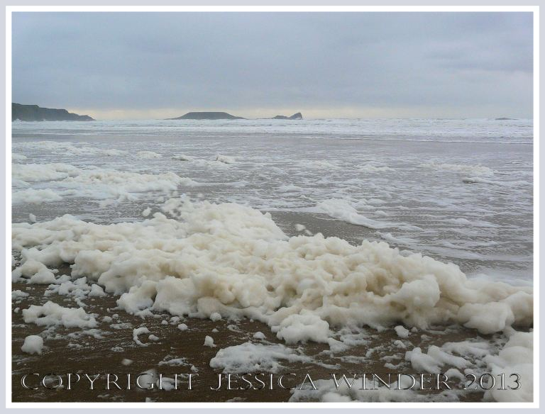 Wet, wild & windy at Rhossili (2) - Piles of sea foam on the sand at Rhossili bay, Gower, South Wales, 14th November 2009, with Worms Head in the background.