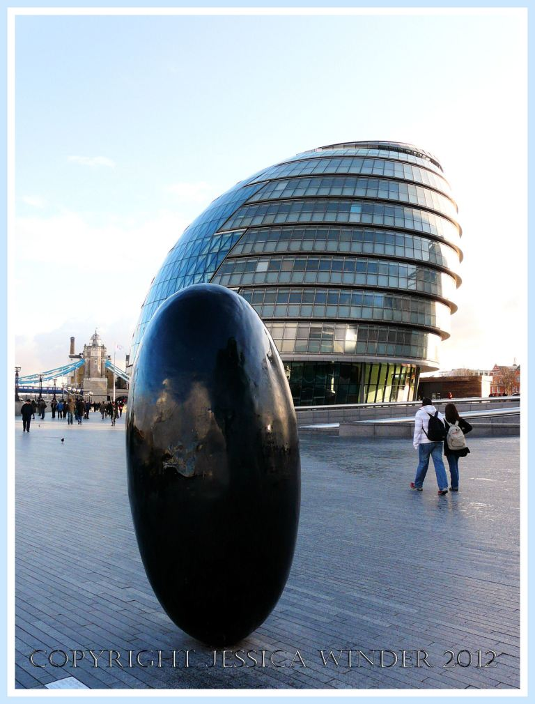 Black egg shaped sculpture on the South Bank, London, UK, close to a lop-sided snail shaped building occupied by City Hall.
