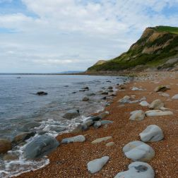 A view looking west towards the rocky end of the beach at Eype, Dorset, UK - part of the Jurassic Coast - showing boulders amongst the shingle and in the shallow sea at the water's edge (8)