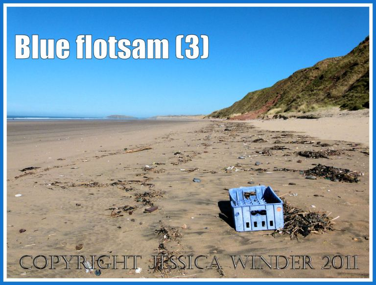 Blue flotsam: Blue plastic crate washed ashore as flotsam on the sandy beach at Rhossili Bay, Gower, South Wales, UK (3)