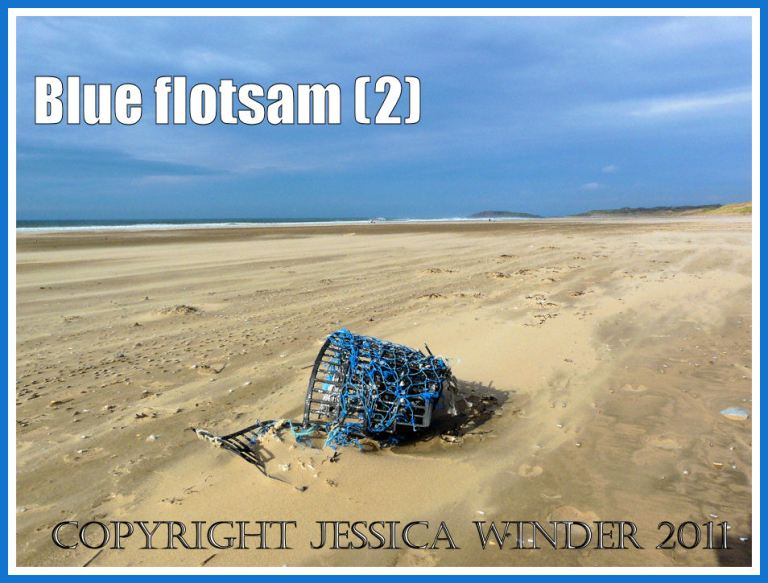 Blue flotsam: An old fishing pot with blue netting washed ashore as flotsam on the sandy beach at Rhossili Bay, Gower, South Wales, UK (2)
