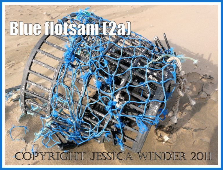 Rhossili flotsam: An old fishing pot with blue netting washed ashore as flotsam on the sandy beach at Rhossili Bay, Gower, South Wales, UK (2a)