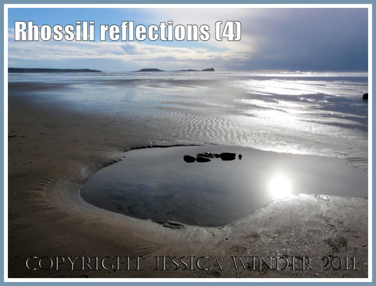 Beach reflections: The sun reflected by pools, wet sand, and the sea at Rhossili Bay, Gower, West Glamorgan, UK - with Worms Head on the horizon (4)
