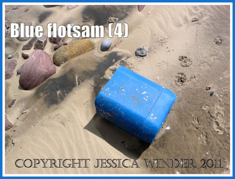 Blue flotsam: Blue plastic container washed ashore as flotsam on the sandy beach at Rhossili Bay, Gower, South Wales, UK (4)