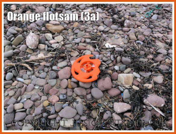 Orange flotsam: Context shot of an orange plastic wheel washed ashore onto the pebble strandline as flotsam (3a)