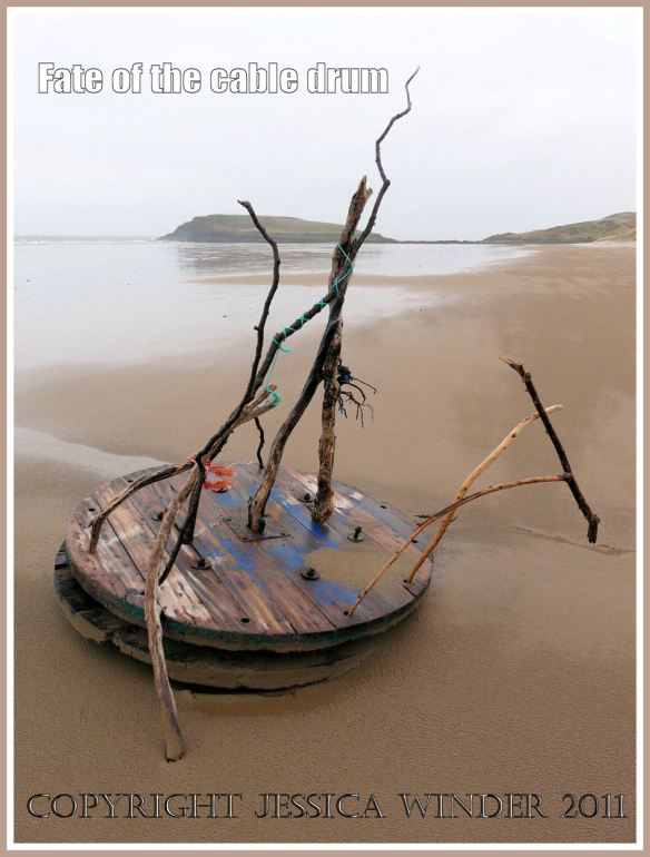 Cable drum on the beach at Rhossili Bay, Gower, West Glamorgan, decorated with driftwood and flotsam, 9th April 2009.