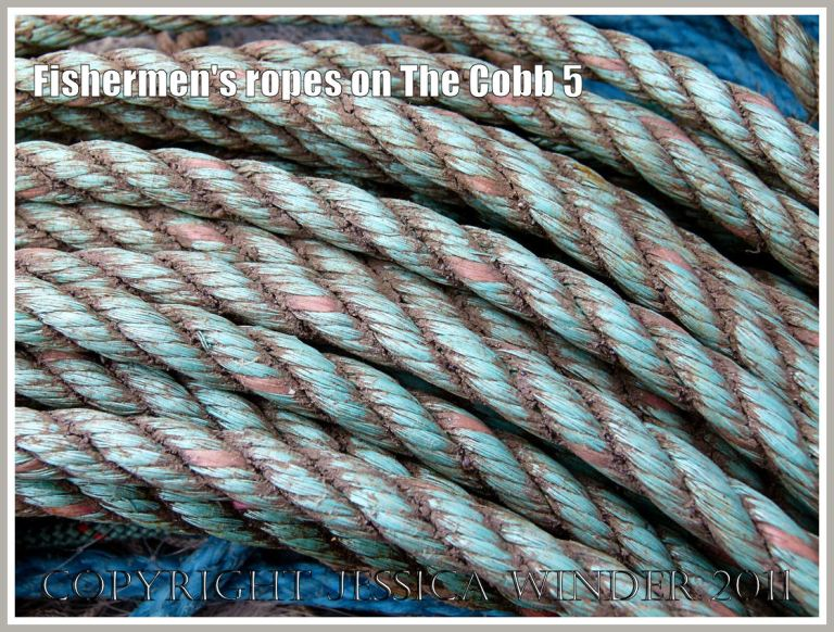 Neatly coiled dirty old ropes from a fishing boat on the quay of the Cobb at Lyme Regis, Dorset, UK (5)