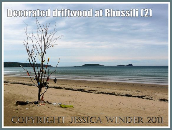 Driftwood tree decorated with flotsam on Rhossili beach against a backdrop of Worms Head, Gower, South Wales, UK, June 2009 (2)