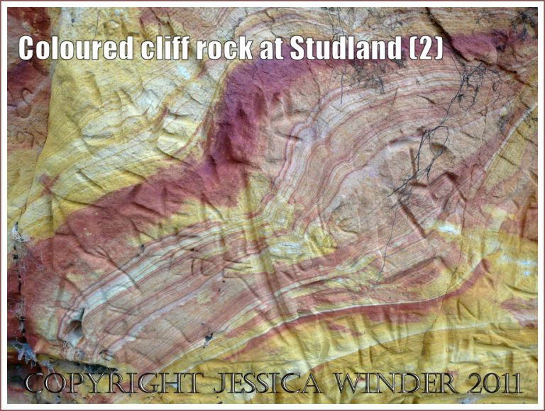 Coloured rock pattern: Red and yellow strata in the cliffs at Studland Bay, Dorset, UK, on the Jurassic Coast - with carved graffiti (2)