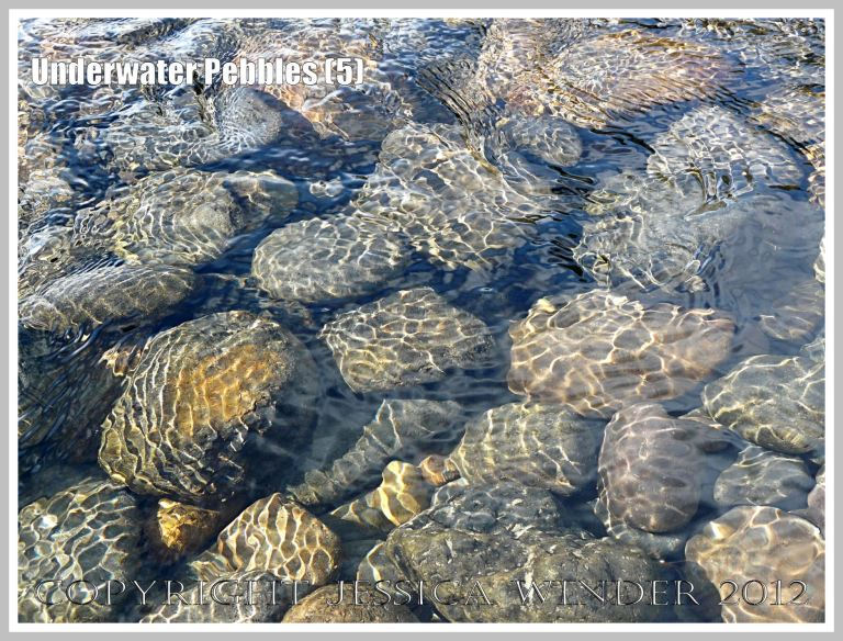 Underwater Pebbles (5) - Pebbles viewed through shallow river water with patterns of reflected sunlight from the water ripples, photographed on the beach in Neptune State Park, south of Yachats, Oregon, U.S.A.
