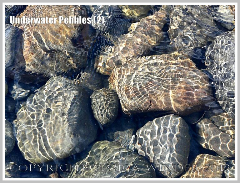 Underwater Pebbles (2) - Pebbles viewed through shallow river water with patterns of reflected sunlight from the water ripples, photographed on the beach in Neptune State Park, south of Yachats, Oregon, U.S.A.
