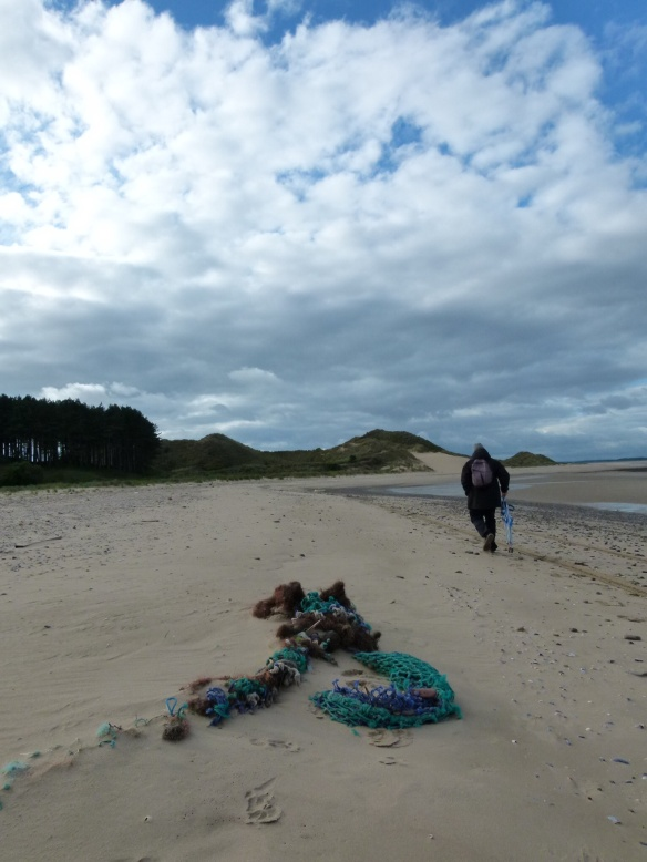 Rope & fishing net rubbish on a sandy shore strand line