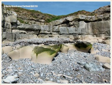 Looking upshore over limestone outcropping amongst pebbles to quarried cliff face on the beach