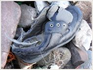 Black shoe without laces washed up on pebbles