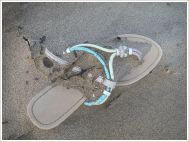 Flip-flop sandal washed ashore on sand