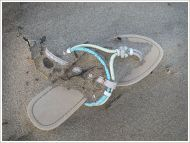 Flip-flop sandal washed ashore on sand
