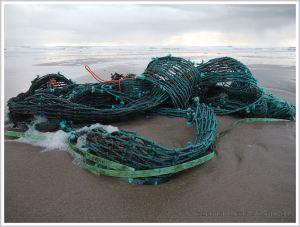 Green fishing net washed up as flotsam on a sandy beach