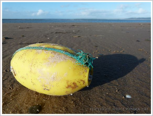Ovoid yellow plastic fishing float with green rope on sand