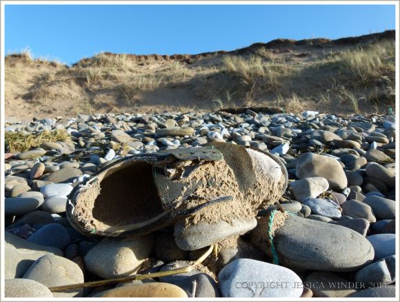 Old shoe full of sand washed up on beach stones