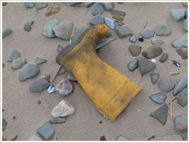 Yellow wellington boot washed up on sand and pebbles