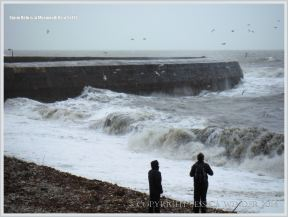 People looking at storm waves near the Cobb wall at Lyme Regis in Dorset