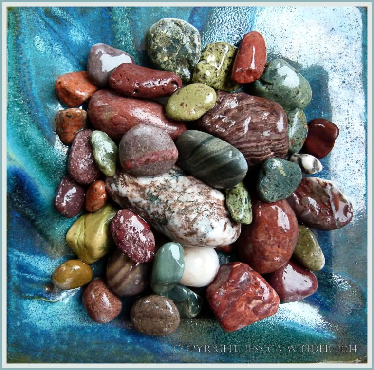 Red, green and patterned pebbles in a dish