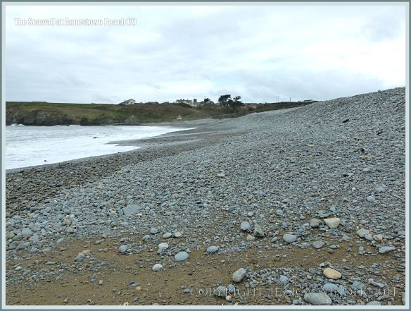 The pebbles on the seashore at Annestown, banked up against a sea wall