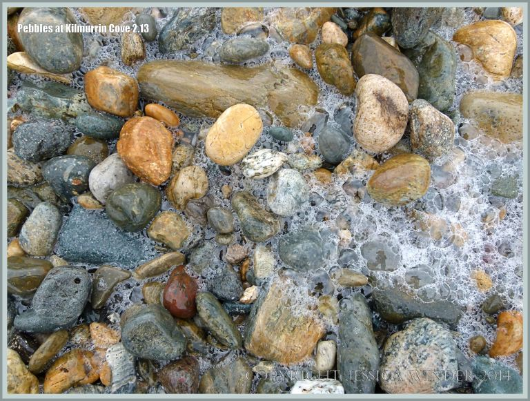 Wet pebbles with sea foam bubbles at Kilmurrin Cove