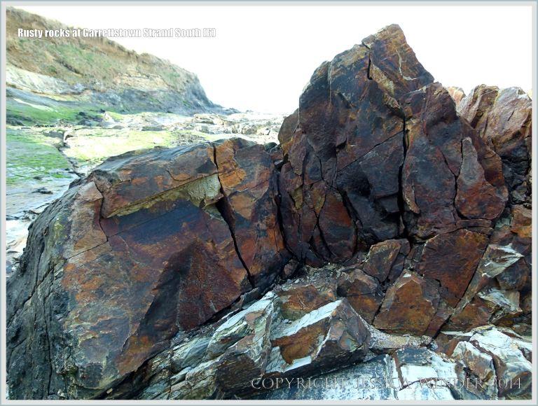 Dark rust-stained rocks on the beach