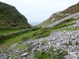 View looking down the limestone scree-clad slopes of Mewslade valley to the sea