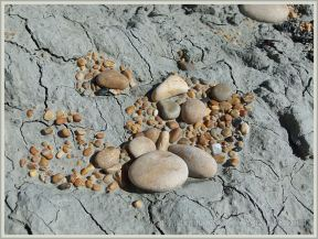 Dried clay on the beach with gravel and pebbles