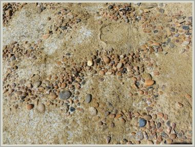 Dried surface of yellow sandy clay with incorporated small pebbles in a recent mud-flow across the shore at Eype in Dorset