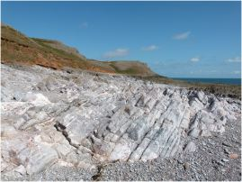 Bare, bleached, rock strata and pebbles on the beach at the Worms Head Causeway