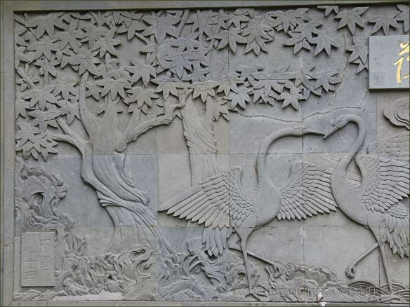 Low relief stone sculpture of cranes