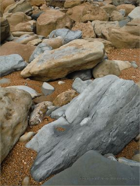 Boulders on the seashore with orange gravel