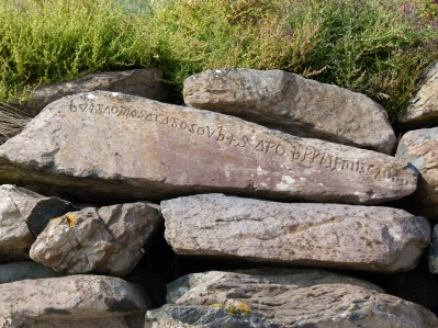Strange carved writing on a riprap boulder
