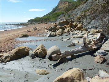 Sedimentary rock boulders and liquified clay on the seashore at the foot of cliffs