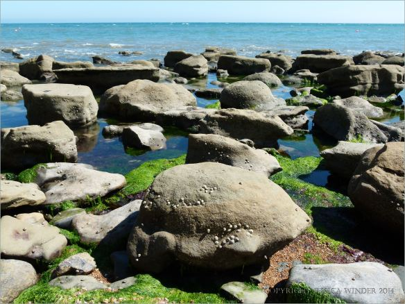 Sedimentary rock boulders on the seashore extending into the sea