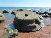 Sedimentary rock boulders on the seashore extending into the sea