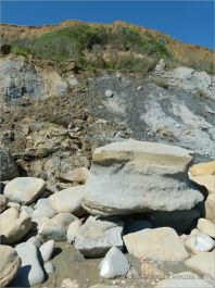 Sedimentary rock boulders on the seashore at the foot of clay cliffs