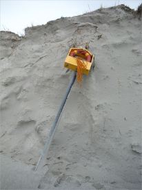 Fallen life belt in container on post on eroded beach sand dune