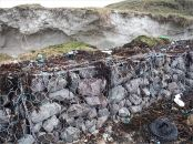 Rock-filled gabion sea defences protecting a tombola from erosion at Dogs Bay