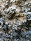 Limestone cliff strata showing bright colour where rocks have recently fallen.