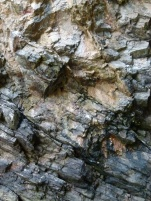 Limestone cliff strata showing bright colour where rocks have recently fallen.
