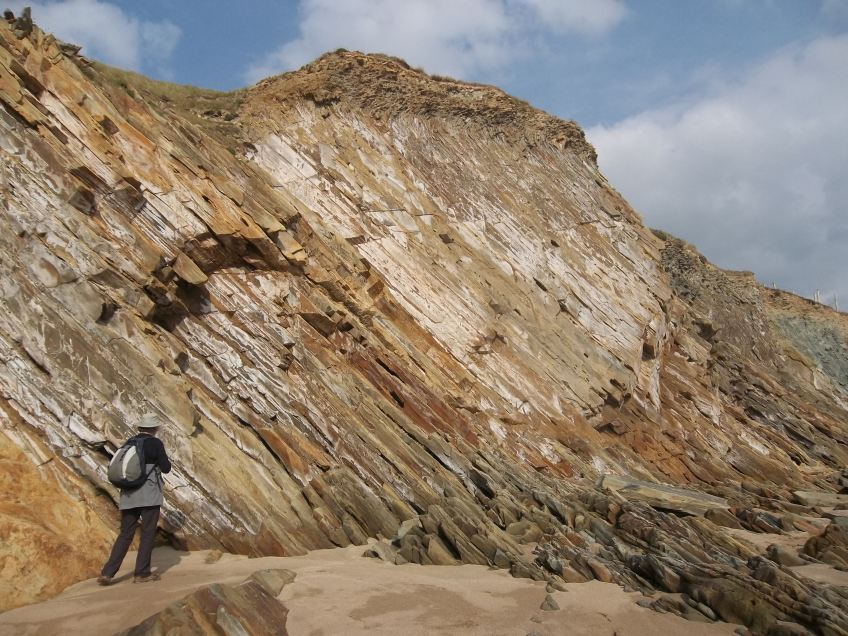 View of cliffs at Clogher Bay with human figure for scale