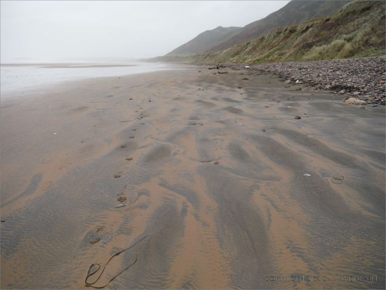 Two-tone sand patterns on a wintry beach beneath Rhossili Down on the Gower Peninsula