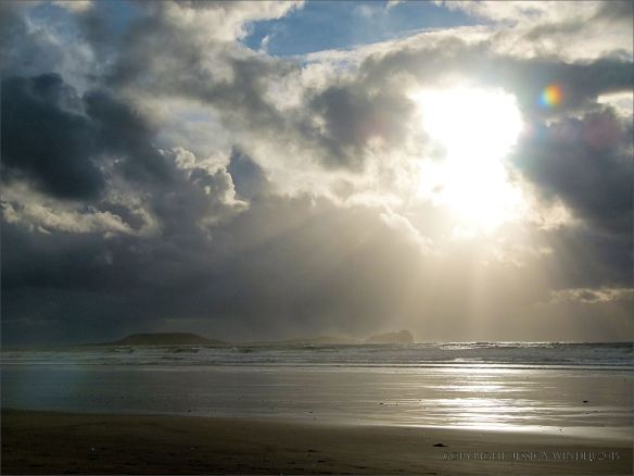 Sun breaking through storm clouds over Worms Head at Rhossili on Christmas Day 2013