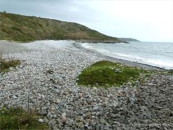 View across the water's edge at Pwll Du Bay
